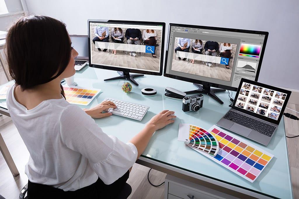 web designer sat at computer monitor
